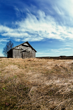 An old barn house stands on the springtime fields of the Northern Finland. The weather is getting warmer, but the nature has not woken up yet. 写真素材