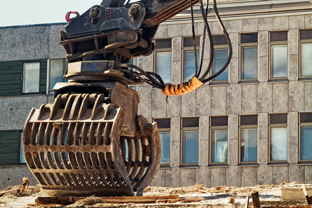 An excavator bucket standing by at a demolition site in the middle of the town of Oulu in the Northern Finland. Stock Photo