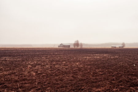 The rain pours over the tiny old barn houses on the muddy fields of the Northern Finland. The spring has not started yet. 写真素材