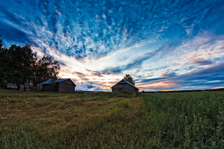 The late summer sun sets beautifully behind the old barn houses in the Northern Finland. The nights are still light, but the sunsets are something to see. Stock Photo