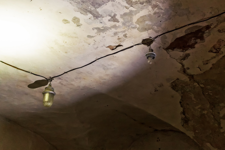 Two old lamps on the ceiling of the death row cell at the old Patarei prison in Tallinn, Estonia. These lamps could have been the last thing the prisoners saw. Banco de Imagens