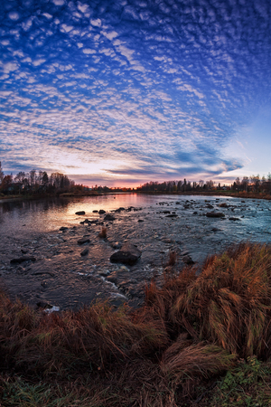The autumn sun sets behind the horizon over the river bend in the Northern Finland. The setting sun emphasized the colors of the autumn in the nature.