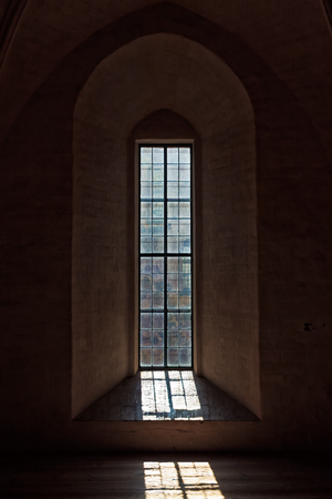 The light comes through the old window of the medieval castle of Turku, Finland. The grill of the window creates an interesting shadow on the floor.