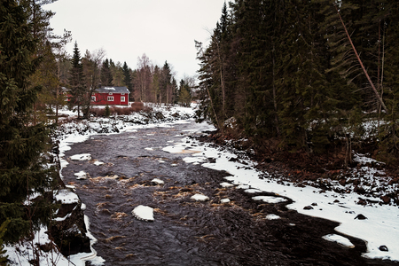 A red house by a snowy river in the Northern Finland. The river is not frozen yet, its not cold enough. 写真素材