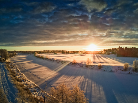 The sun rises over the frozen river on a cold morning in the rural Finland. Everything is covered with the driven snow.