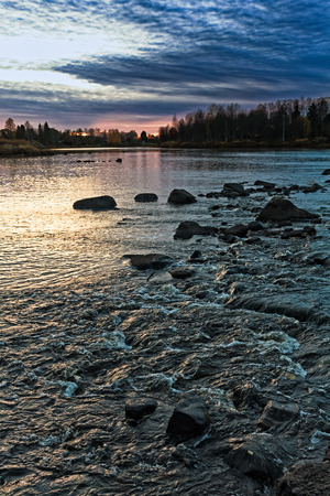 The sun sets on an autumn evening over the river rocks at the rural Finland. The sky is pretty dramatic on the autumn nights like this. 版權商用圖片