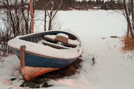 An old fishing boat covered with snow on a cold morning at a fishing village in the Northern Finland. The sea is frozen, you cant fish with boats.