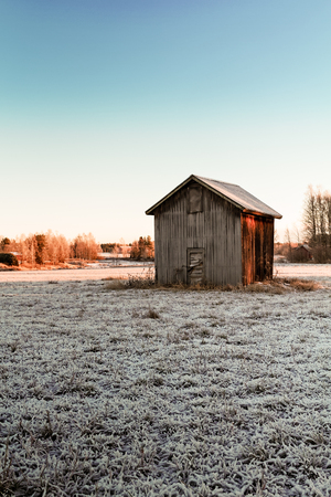 A tiny barn house stands on the frosty fields of the Northern Finland. The autumn sun warms up the cold wooden walls of the building.