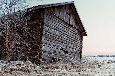 The wall of an old barn house is covered with frost on a cold morning at the rural Finland.