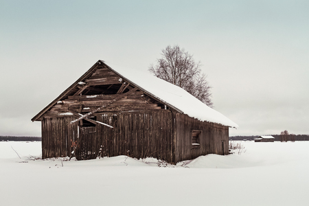 An old abandoned barn house stands on the snowy fields of the rural Finland. The weather is cold and the wooden walls of the building are covered with frost.