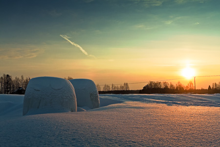 Two hay bales wrapped in plastic have almost sunken in the snow on a field in the rural Finland. The winter sun sets early in the background.