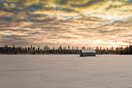 The sun sets behind a small barn house standing alone on a snow covered field at the rural Finland. The cold day ends with a dramatic sky.