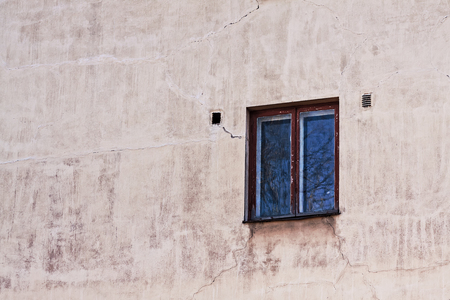 An old window on a building exterior in Tallinn, Estonia. Both the window and the wall have seen better days. Imagens