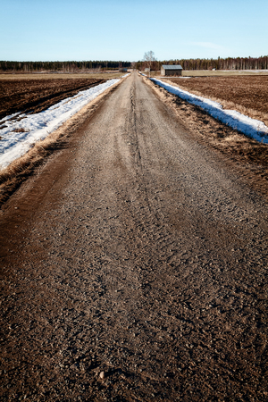 A gravel road leads through the fields in the springtime at the rural Finland. There is still snow on the ground in the middle of April.