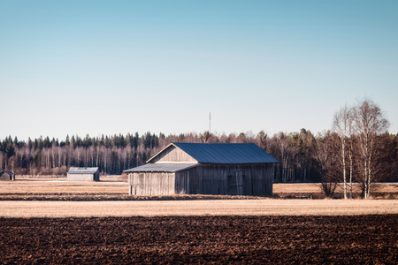 The old barn houses bathe in the springtime sun at the Northern Finland. The sun starts to warm up the frozen ground.