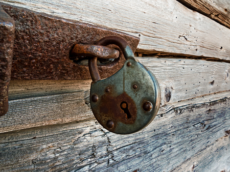 An old lock hangs on a wooden door at the old town of Kalajoki, Finland. The old fishing village has been preserved as a museum district. Imagens