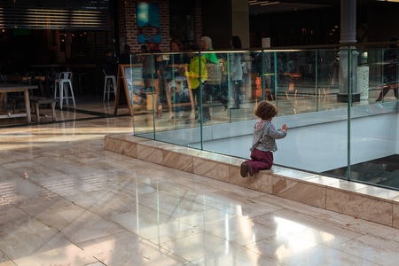 A small child is watching the people rushing at a shopping centre in Serris, France. The child has all the time in this busy world.