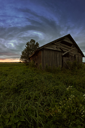 The clouds create a round formation over an old barn house on a late summer night at the Northern Finland. The view is almost sci-fi like.