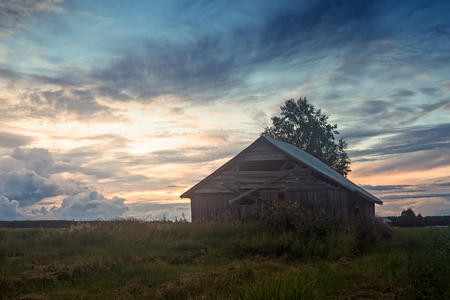 An old barn house against a beautiful sunset on a summer night at the rural Finland. This kind of sunsets are very typical in the area.