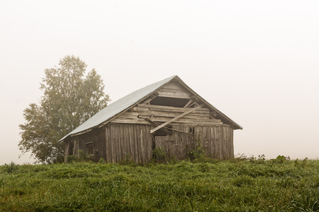 An old barn house stands on the summer fields on a very foggy morning at the rural Finland. The summer is almost over and the air is getting colder.