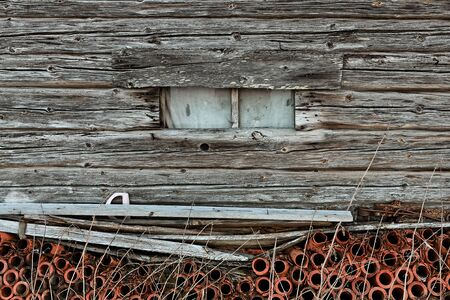 A window in an old wooden barn house at the rural Finland. The pipes under the window are made of clay.