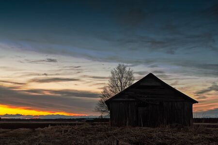 The sun sets beautifully behind an old barn house at the rural Finland. The sunset colors the clouds dramatically.