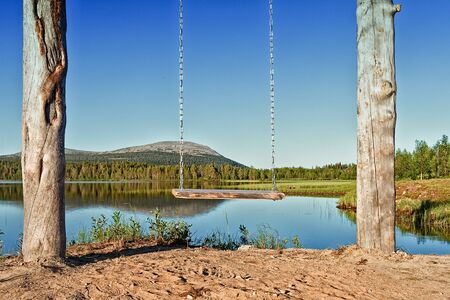 A wooden swing hangs by the still water of a beautiful lake at the Finnish Lapland. It is midsummer and the sun does not set all night.