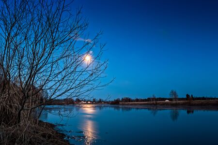 The full moon shines on a clear spring night at the Northern Finland. The moonlight reflects on the still water of the river. Imagens