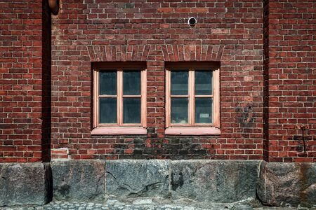 Two windows on a brick wall of an old industrial building at Helsinki, Finland.