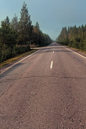 The mist covers the empty road on a late summer morning at the rural Finland. There are nobory driving these roads in the early hours.