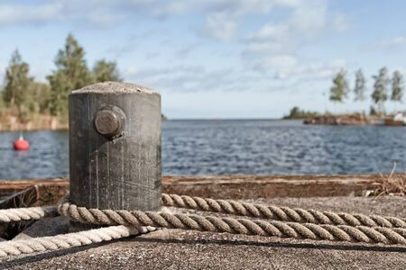 An old metal bollard on a pier at the fishing harbour of the town of Kalajoki, Finland. The ropes belong to an old galeas at the harbour.