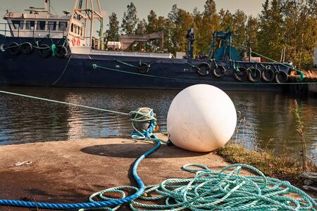An old white buoy lies on the pier at the fishing harbour of the town of Kalajoki, Finland. Its early autumn and the fishing boats are not on the sea. Imagens