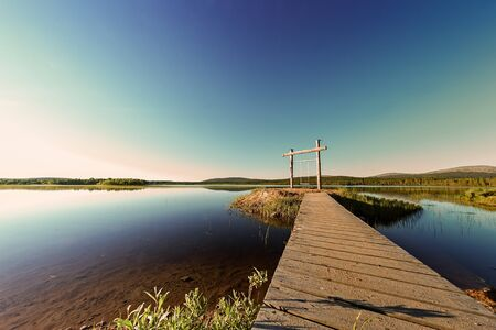 A wooden path leads to a swing by a lake in the Finnish Lapland. The swing is built on an island in a lonely lake.