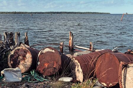 Old barrels have been left to rot by the remains of an old wooden pier at the fishing harbour of Kalajoki, Finland. Imagens