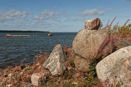 A pile of large rocks by the sea at the fishing harbour of Kalajoki, Finland. The wind is blowing hard from the sea and bending the willowherbs on the shore.