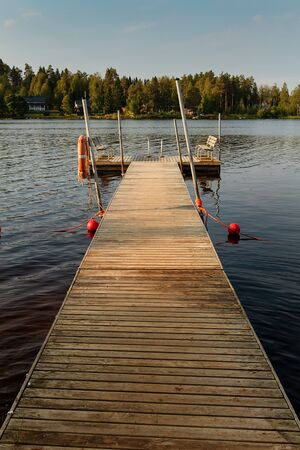 A pier has two wooden benches for the swimmers by a lake at the rural Finland. The autumn morning is cold, so nobody is going for a swim.