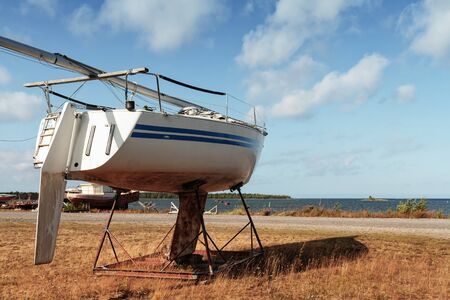 An old sailing boat supported on the ground at the fishing harbour of Kalajoki, Finland. The boat seems to be eagerly waiting to get to the sea.