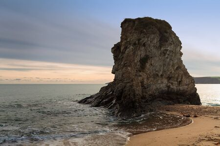 A giant rock at the Carlyon Bay in Cornwall, England. The sun sets beautifully over the sea. Stock Photo