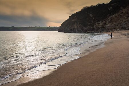 A boy looking at the sea on a beach in Cornwall, England. The evening sun sets beautifully in the background.