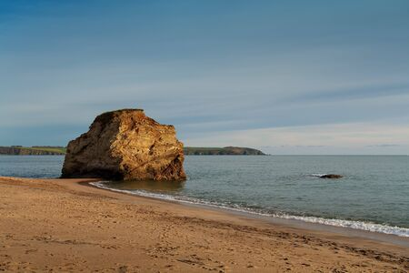 A giant rock rises from the sea at Carlyon Bay in Cornwall, United Kingdom. Stock Photo