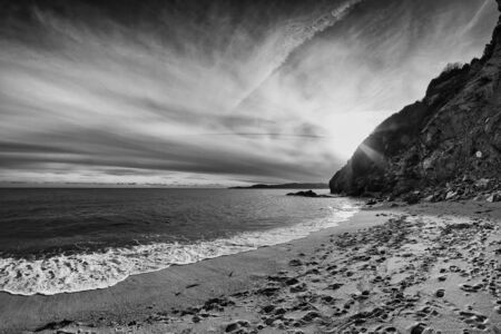 The sun sets beautifully behind the cliffs at St. Austell, Cornwall, England. The people have already left the beach.