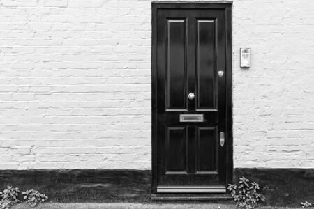 A typical wooden door on a painted brick wall in London, United Kingdom. The green plants create a contrast to the black and white architecture. Stock Photo