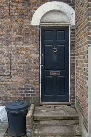 A plastic trash bin is standing by an old door in London, England. The brick wall has seen better days. Stock Photo