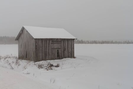 An old abandoned barn house stands on the snowy fields at the rural Finland. The snow storm is covering everything in white. Imagens