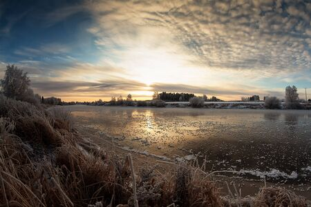 The sun rises over the rive on a cold morning at the rural Finland. The river water is slowly freezing. Stock Photo