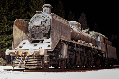 An old steam engine covered in frost on a very cold winter night at a rural town in Finland.
