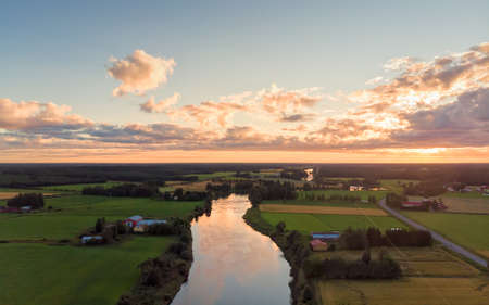 The late summer sun sets over the river at the rural Finland. The sky is very dramatic in this aerial view.