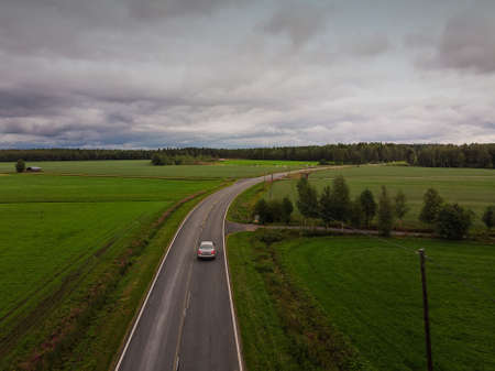 A lonely car driving on a country road under the stormy skies at the rural Finland.