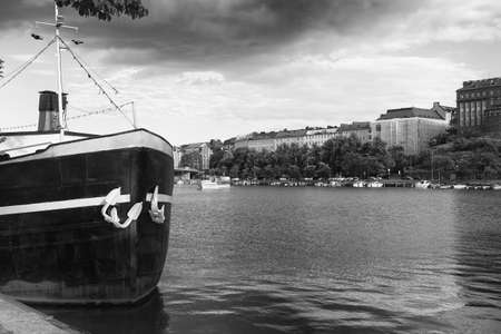An old steam boat is standing at the harbor of Helsinki, the capital of Finland, on a summer day. A ferry is slowly approaching the pier. Stock Photo