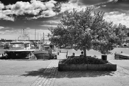 Two elderly women are sitting in the shade on a warm day at the harbor of Kotka, Finland. The harbor is almost like the living room of the townspeople. Stock Photo